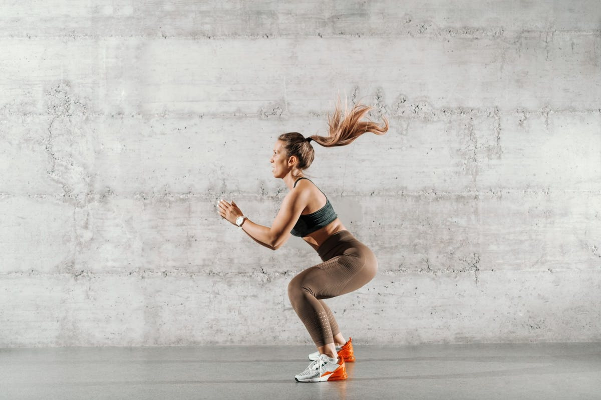 Strong woman squatting with pony tail