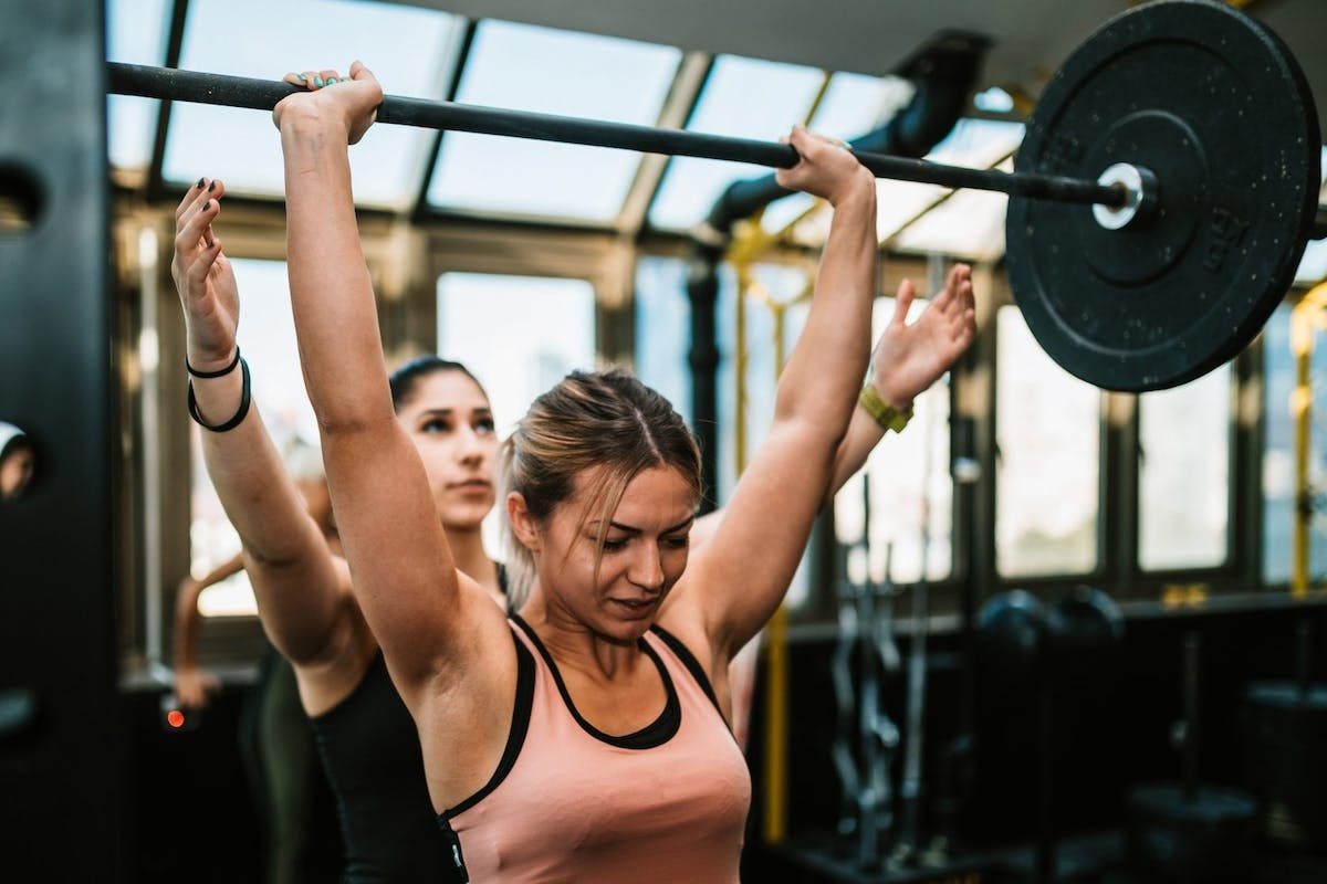 Woman lifting weights whilst being supported by her personal trainer