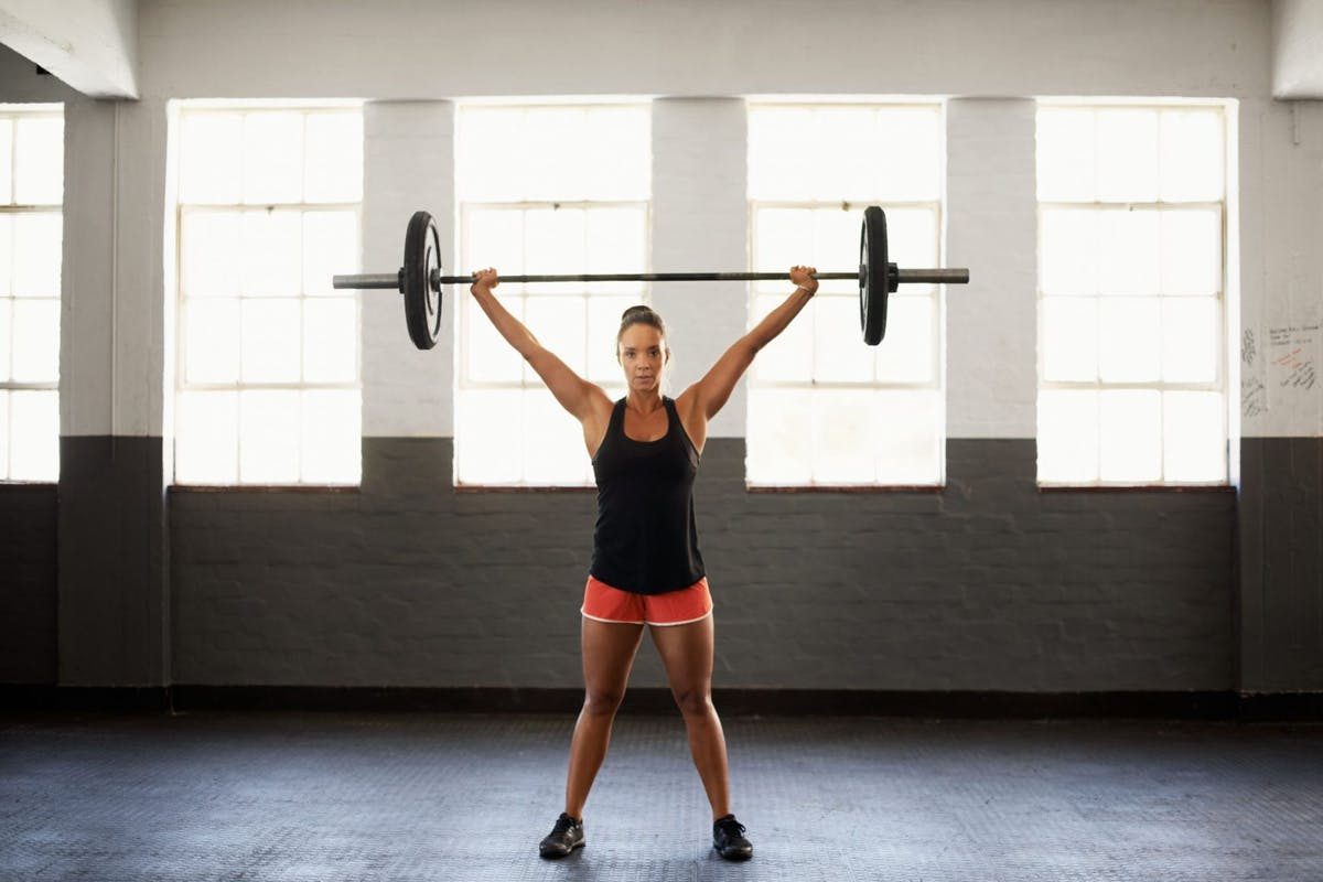 Stong woman lifting weights in the gym