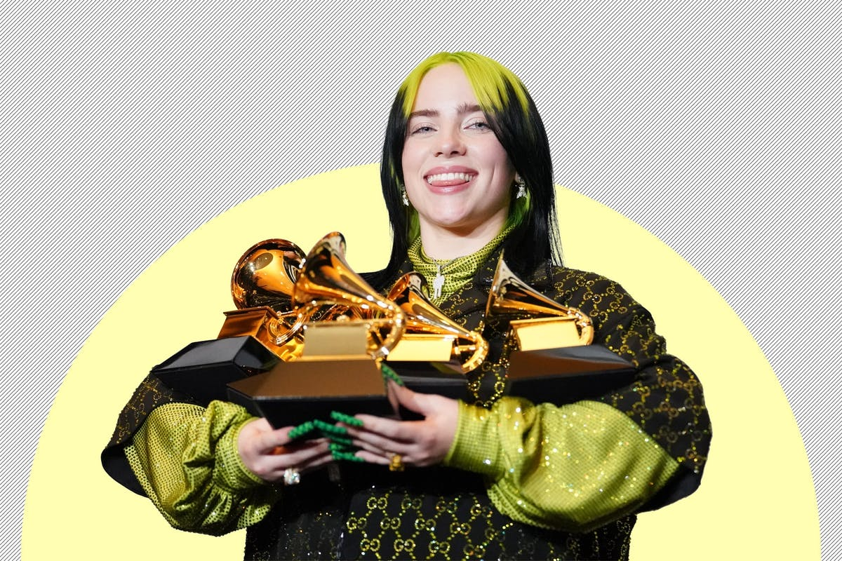 Billie Eilish holding her five Grammy awards