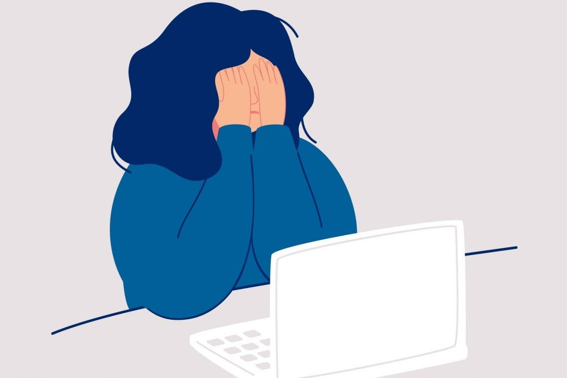 A woman covering her face at her computer