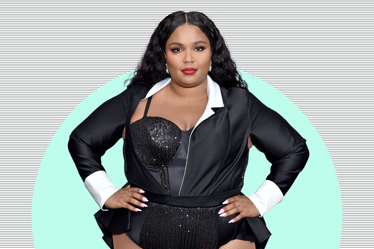 Lizzo stands with her hands on her hips against a graphic background
