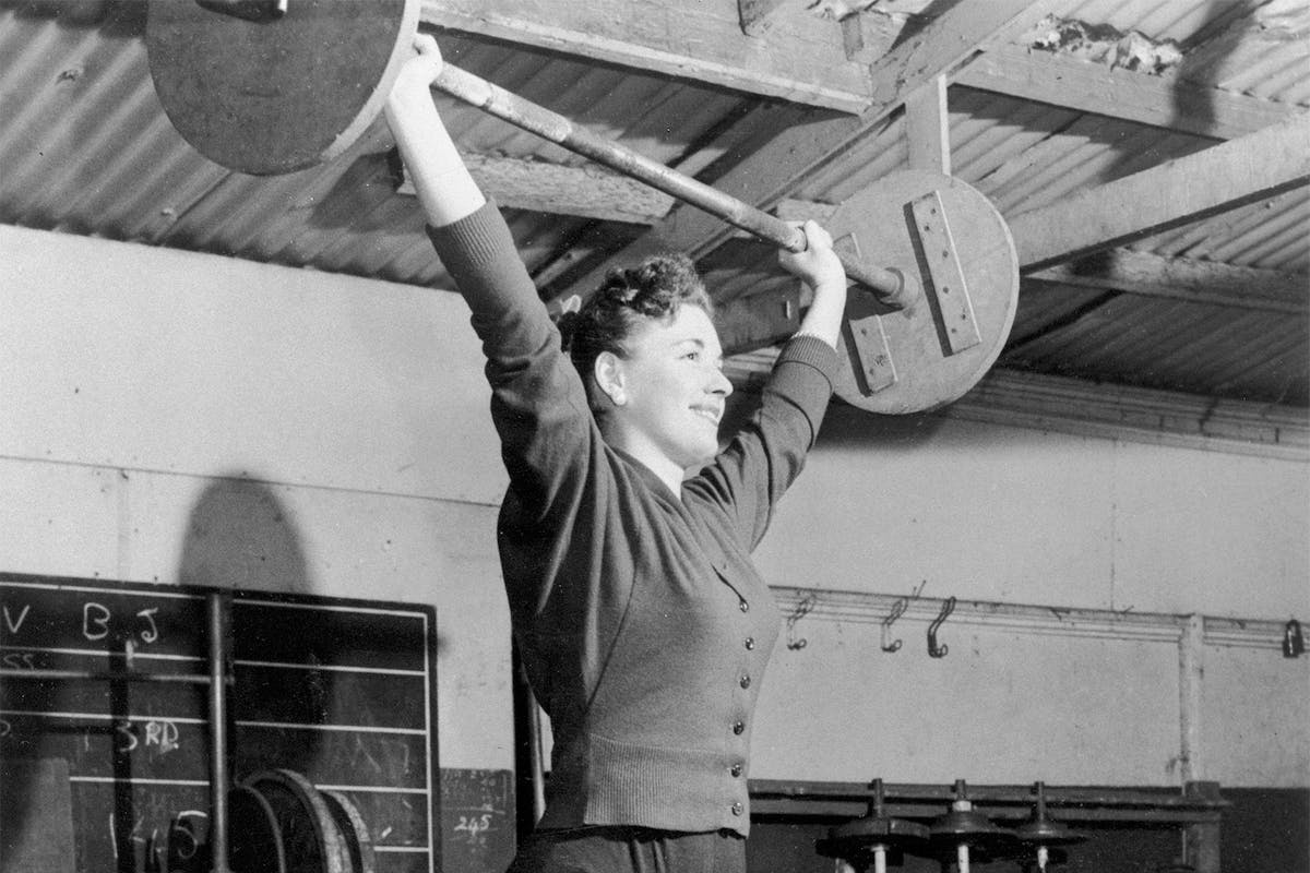 Black and white photo of woman lifting weights at the gym