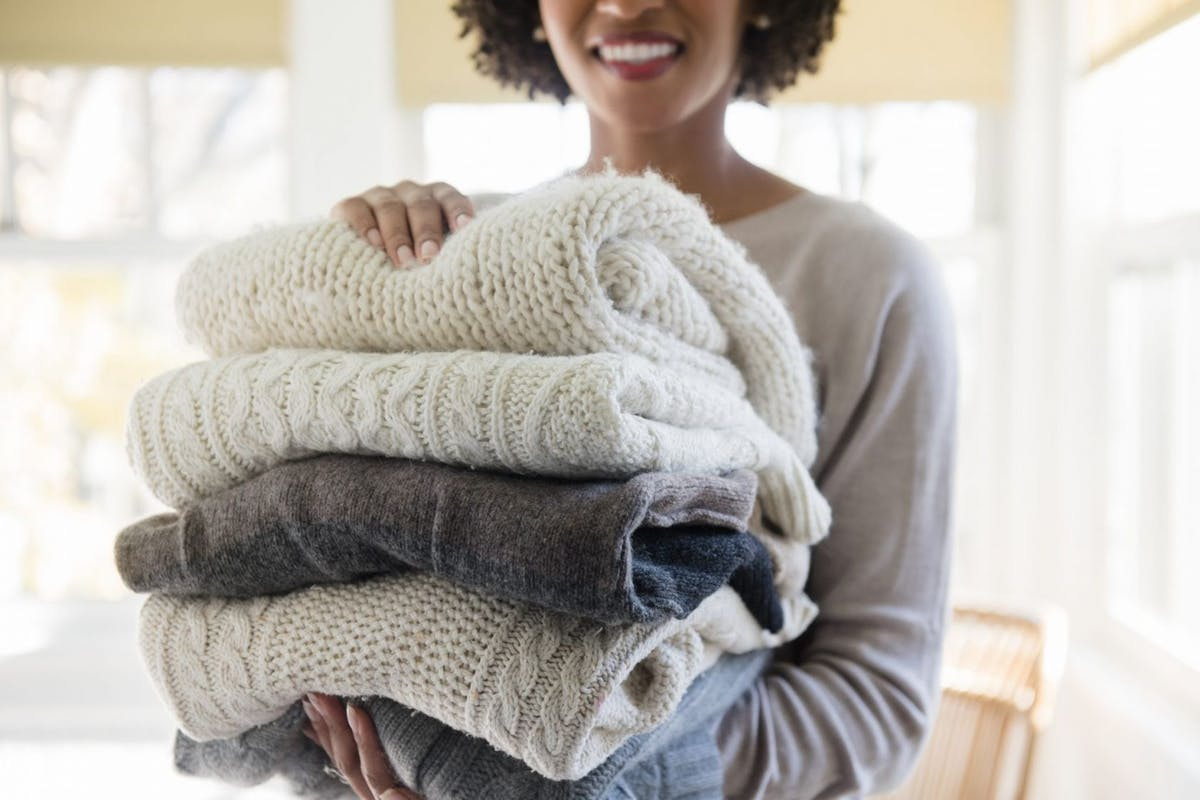 Woman holding a stack of folded knitted blankets