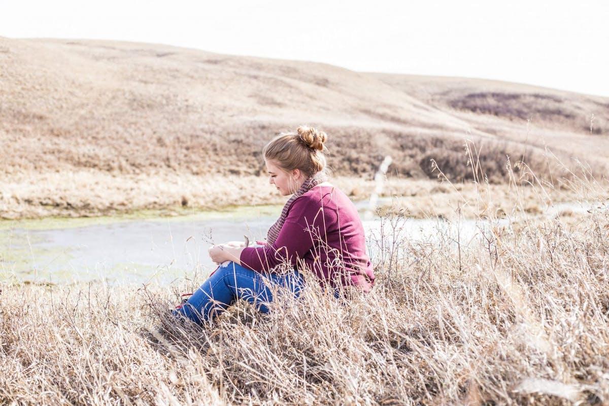 Woman sitting alone in cornfield