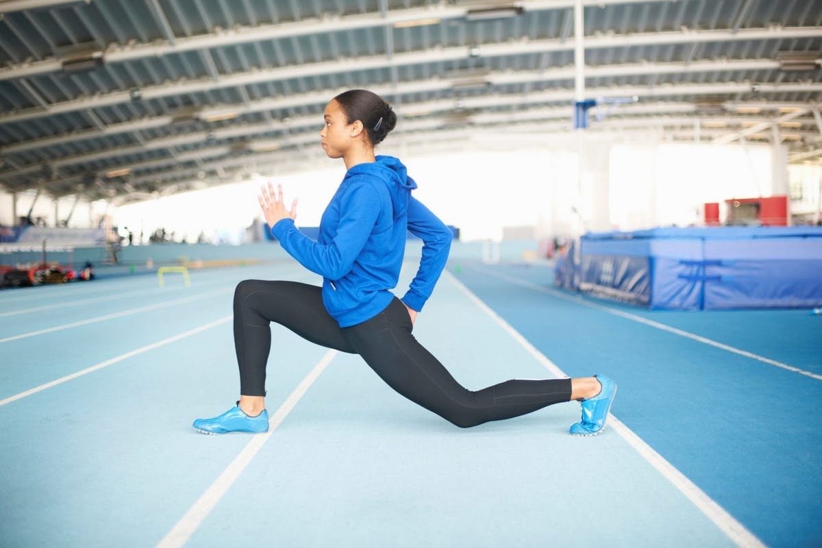 Woman lunging on a running track