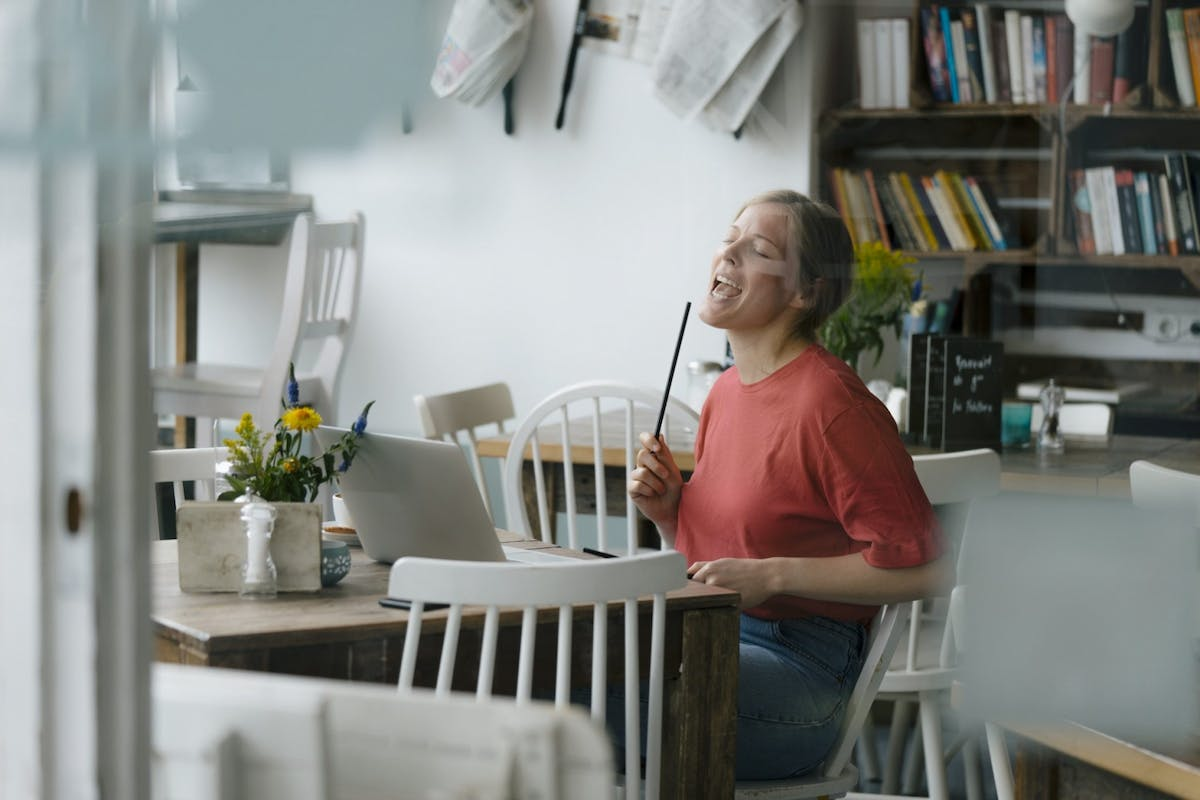A woman singing at her kitchen table