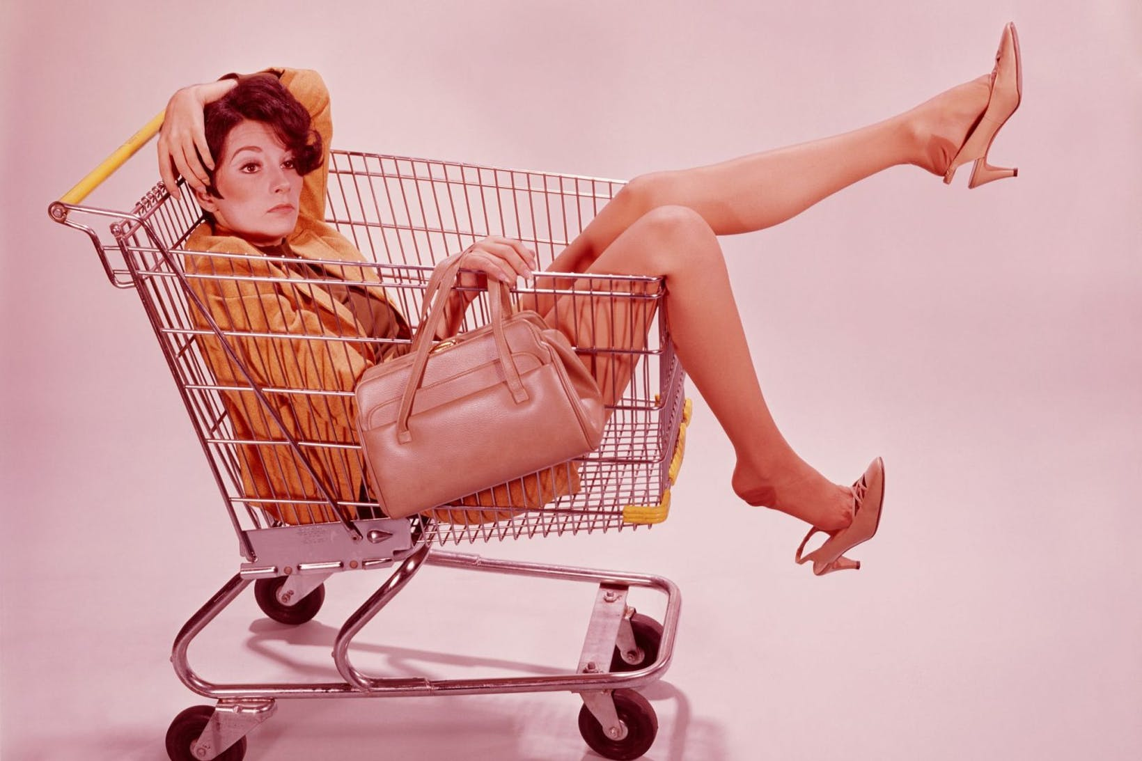 auburn haired woman from 1960s with shades of brown suit and beige purse, which is delicately draped over the edge of a shopping cart with banana yellow bumpers and handles, is sitting in a basket with an intense look on her face, hand dropped across her face, and one leg in the air with shoes half falling off