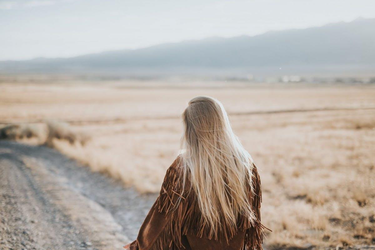 Blonde Nordic woman walking along a road