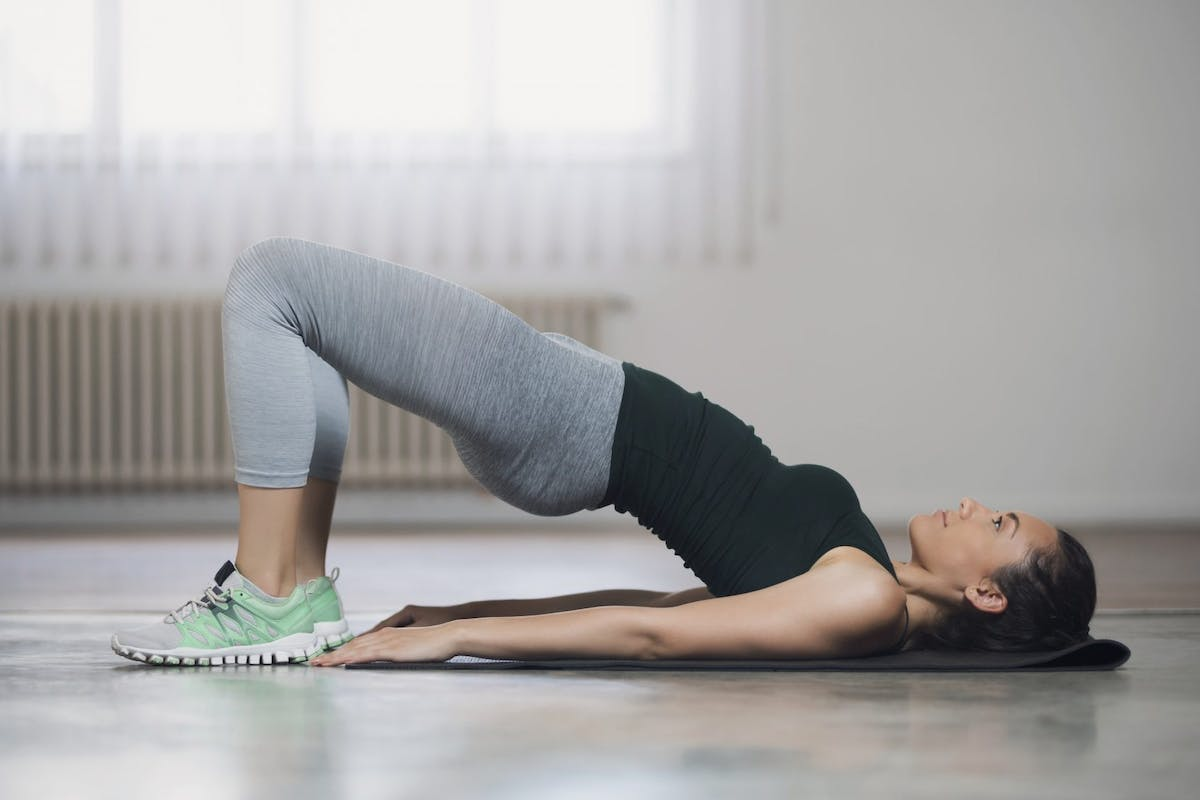 A woman doing glute bridges during a lower body workout.