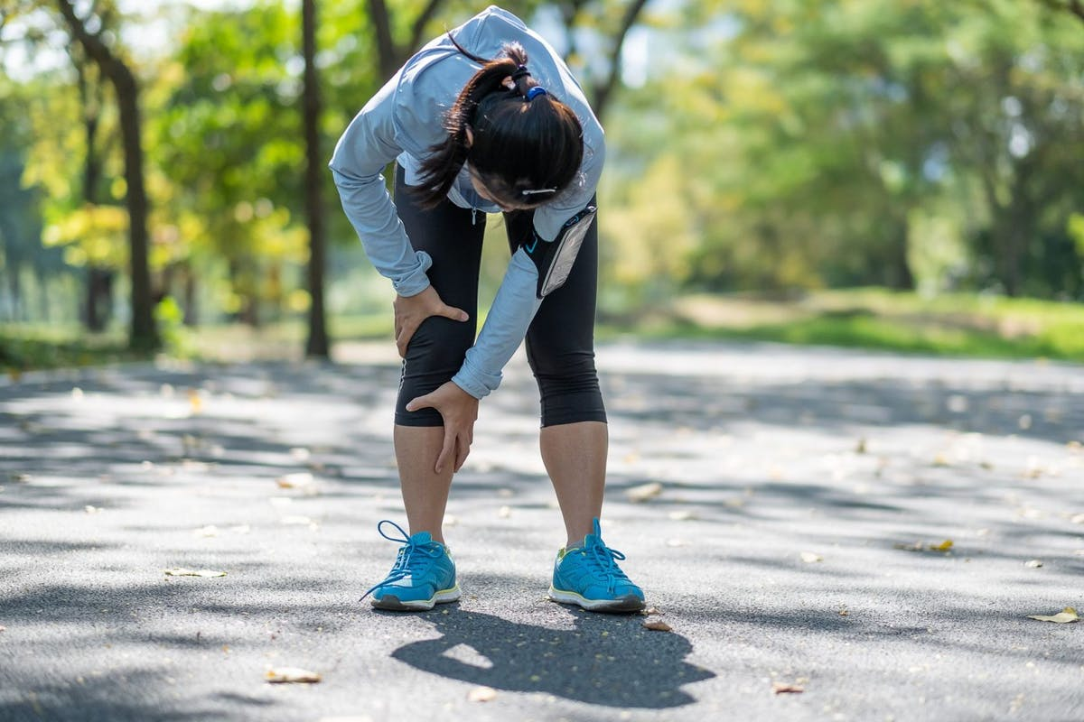 Woman holding a sore knee whilst out running