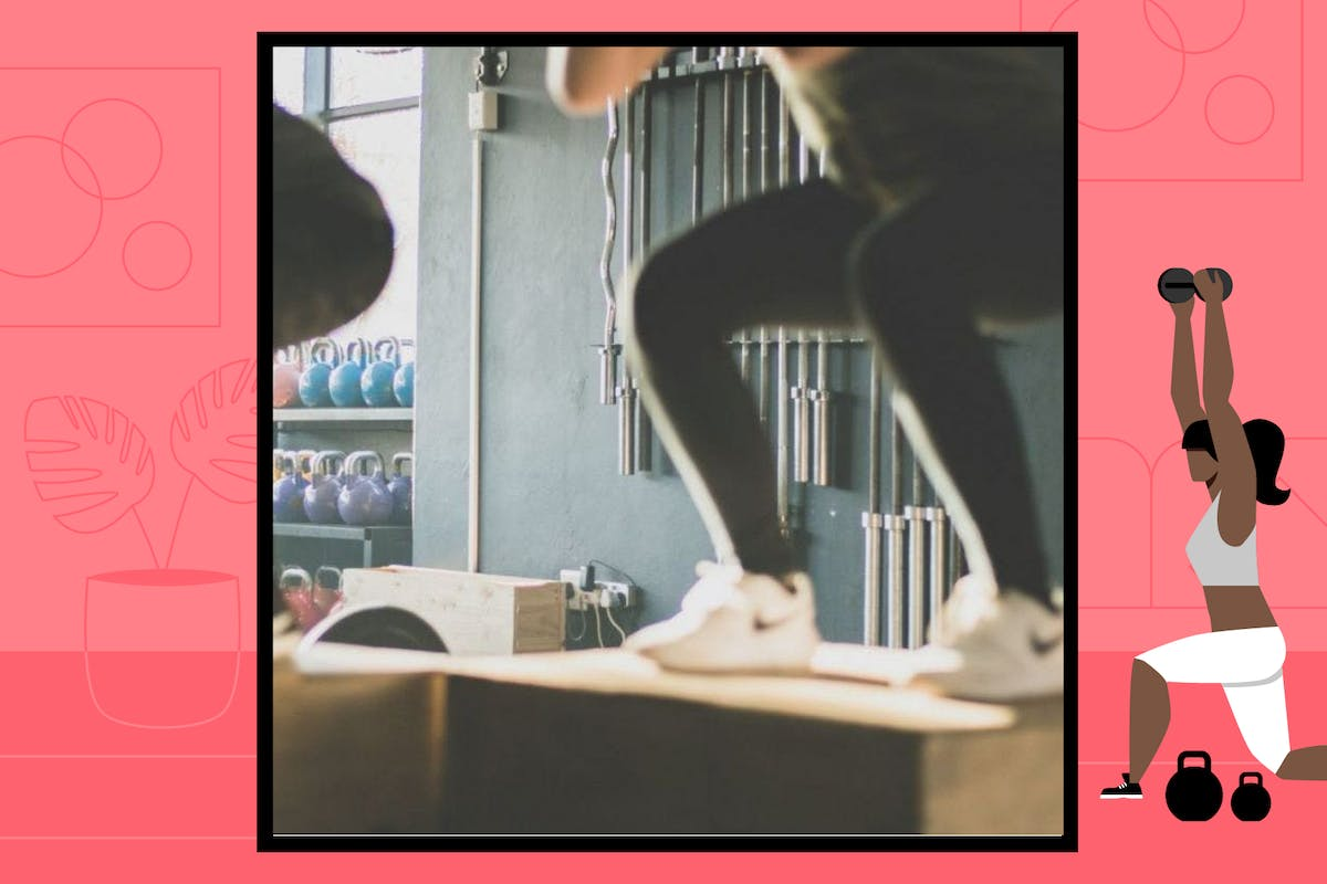 Two women do box jumps in the gym.