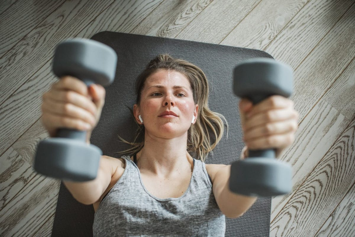 A woman doing a chest press on an exercise mat while working out from home.