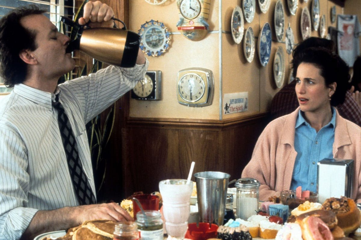 Bill Murray puts down a pitcher of coffee with Andie MacDowell in a scene from the film 'Groundhog Day', 1993. (Photo by Columbia Pictures/Getty Images)
