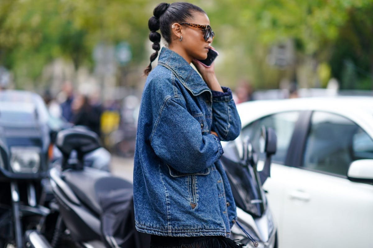 A guest wears a denim jacket to fashion shows