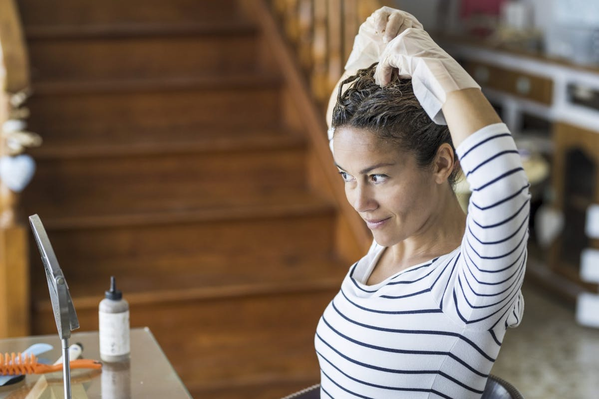 woman-applying-hair-dye-in-mirror