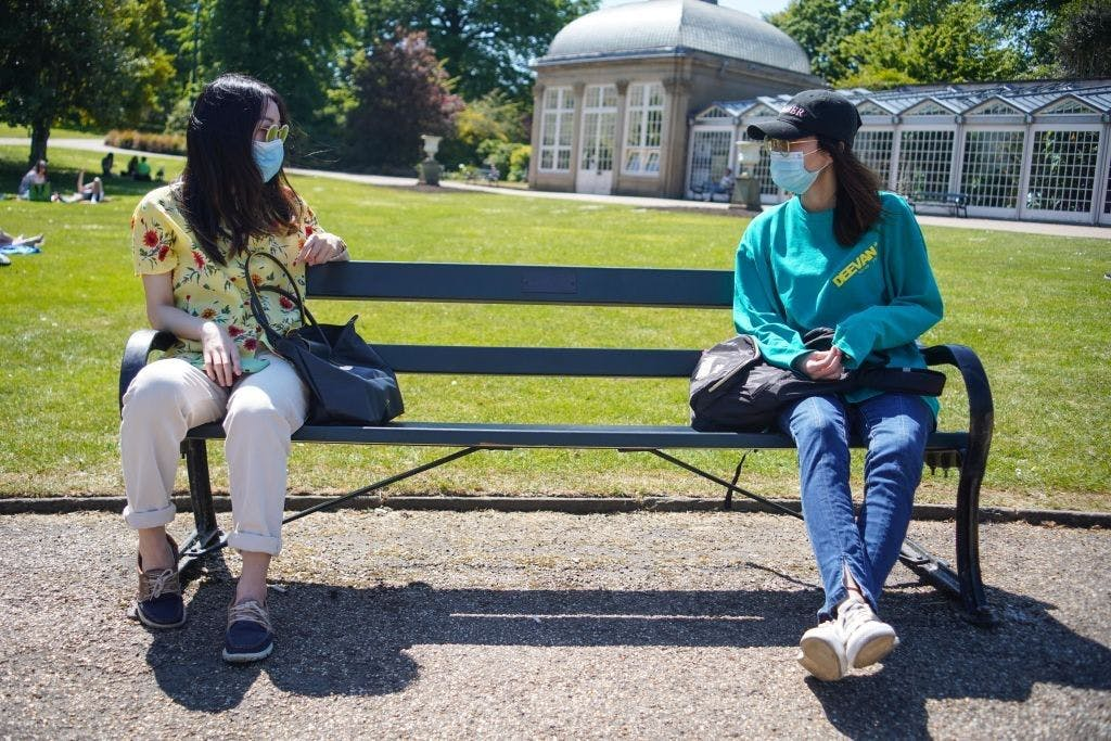Two friends wearing face masks sit on a bench as they maintain social distancing at the Botanical Gardens , Sheffield, UK on a warm day on 22nd May 2020. (Photo by Giannis Alexopoulos/NurPhoto via Getty Images)