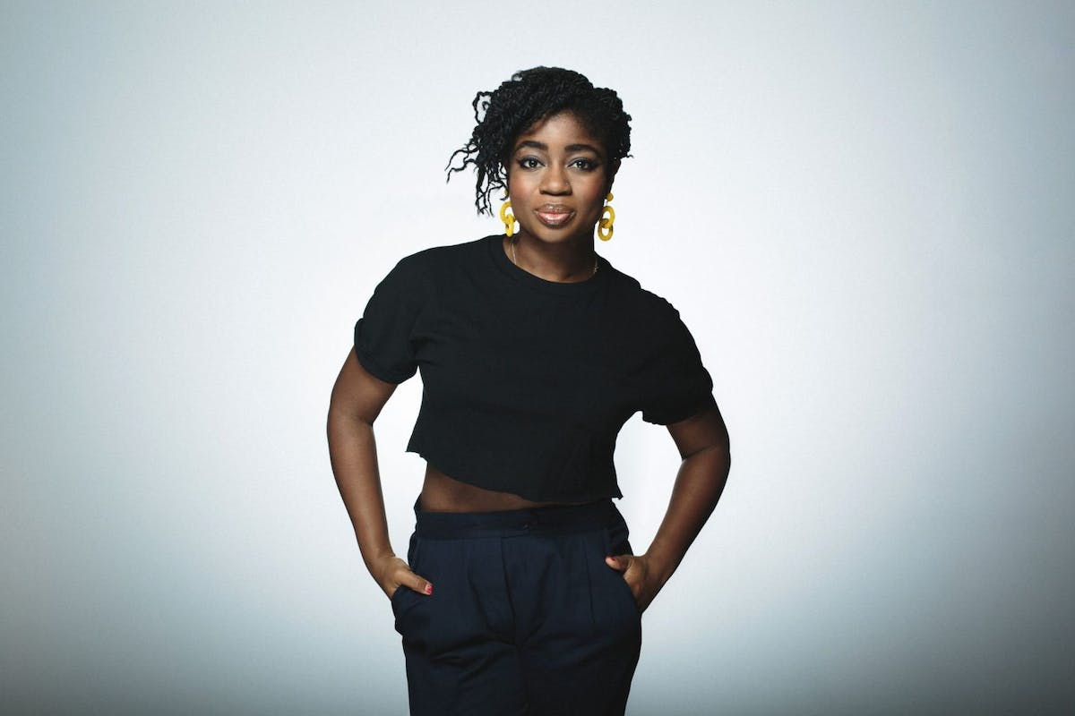 Clara Amfo stands against a grey backdrop in a BBC press shot