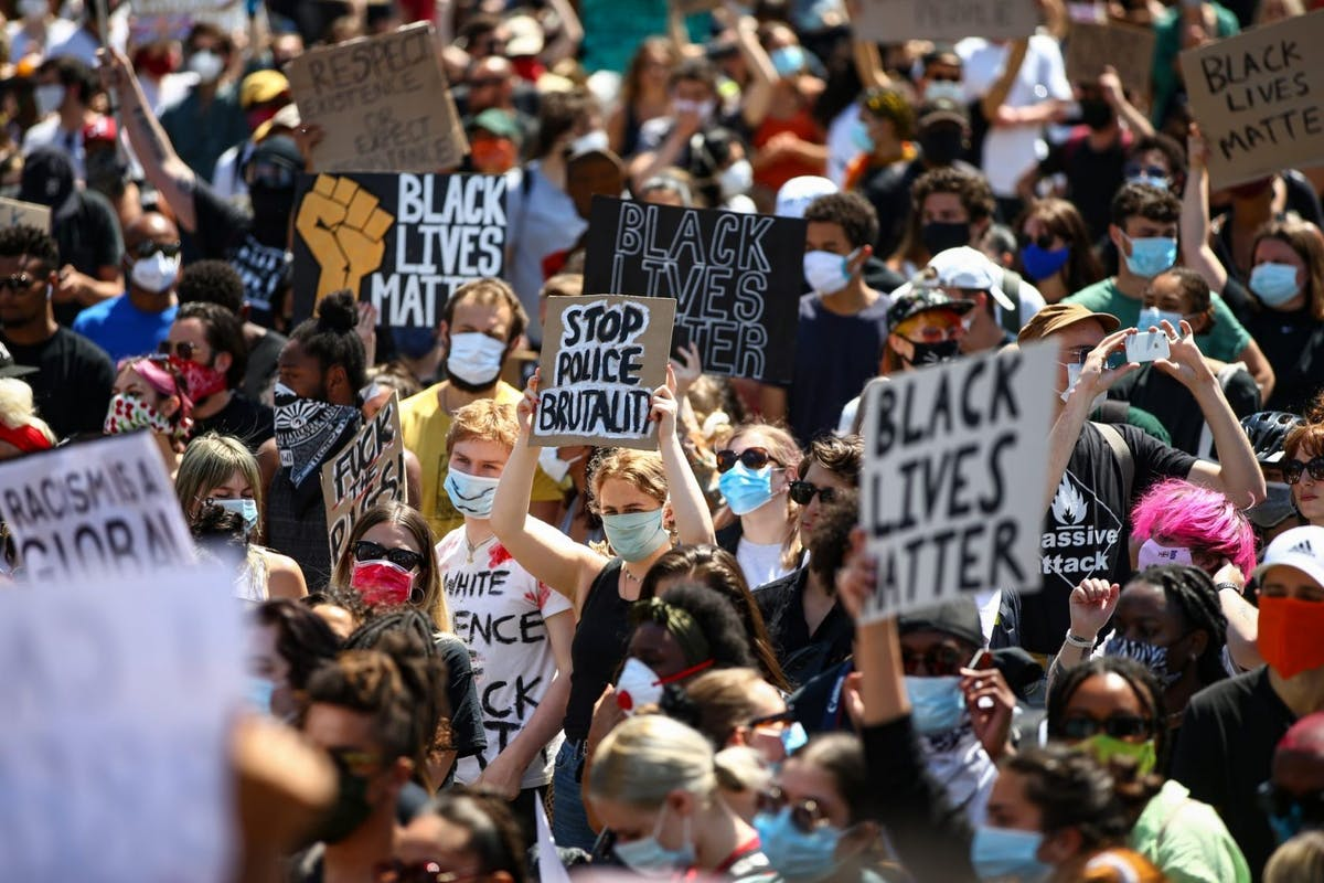 People hold placards as they join a spontaneous Black Lives Matter march through central London to protest the death of George Floyd in Minneapolis and in support of the demonstrations in North America on May 31, 2020 in London, United Kingdom.