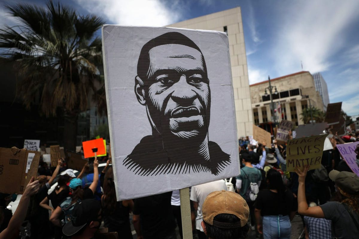 A protester holds a sign with an image of George Floyd during a peaceful demonstration over George Floyd's death outside LAPD headquarters on June 2, 2020 in Los Angeles, California.