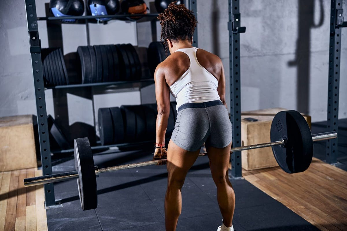 A woman bending over with a barbell in hand to do a deadlift