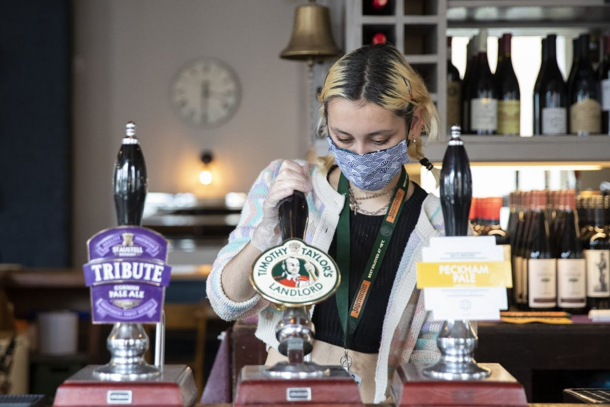 Employees pull pints at the Lordship pub in East Dulwich on July 04, 2020 in London, England. The UK Government announced that Pubs, Hotels and Restaurants can open from Saturday, July 4th providing they follow guidelines on social distancing and sanitising. (Photo by John Phillips/Getty Images)