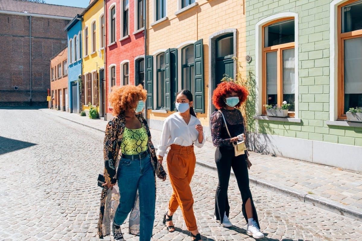 Three women walking down the street wearing masks