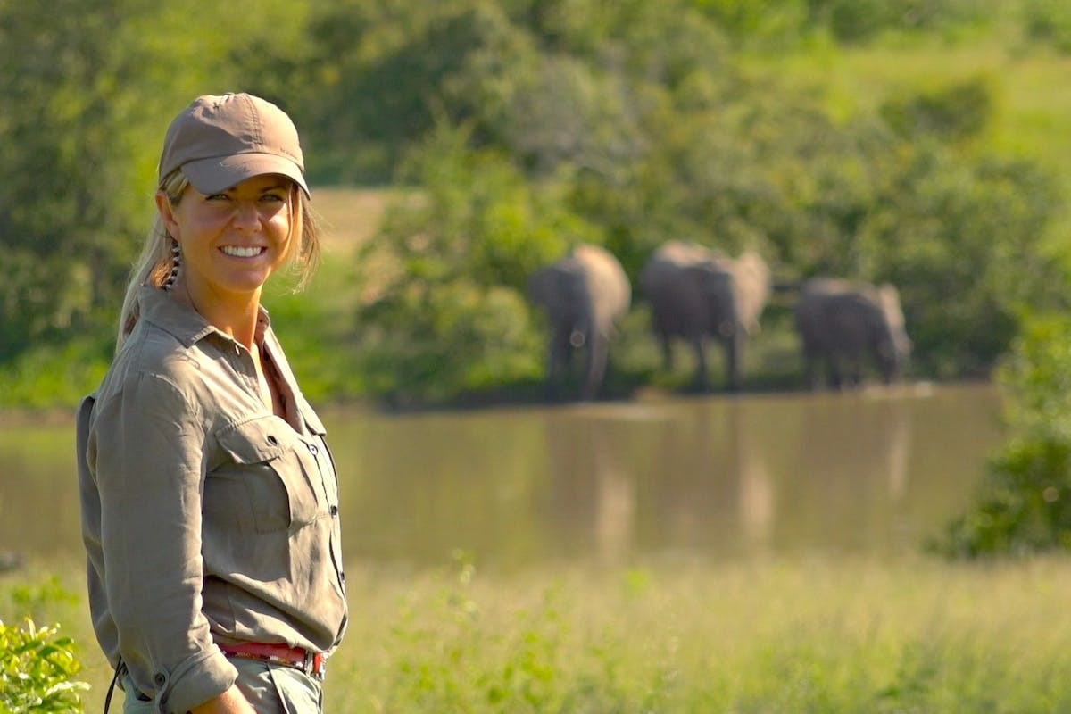 Presenter Lauren Arthur on safari in South Africa with elephants in the background