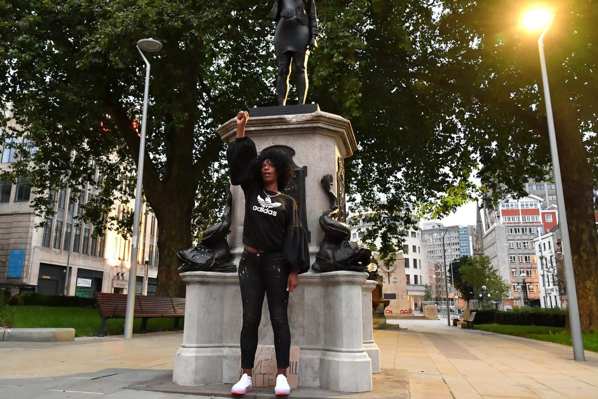 Black Lives Matter protestor Jen Reid poses for a photograph in front of a sculpture of herself, by local artist Marc Quinn, on the plinth where the Edward Colston statue used to stand on July 15, 2020 in Bristol, England. A statue of slave trader Edward Colston was pulled down and thrown into Bristol Harbour during Black Lives Matter protests sparked by the death of an African American man, George Floyd, while in the custody of Minneapolis police in the United States of America. The Mayor of Bristol has since announced the setting up of a commission of historians and academics to reassess Bristol's landmarks and buildings that feature the name of Colston and others who made fortunes in trades linked to slavery. (Photo by Matthew Horwood/Getty Images)