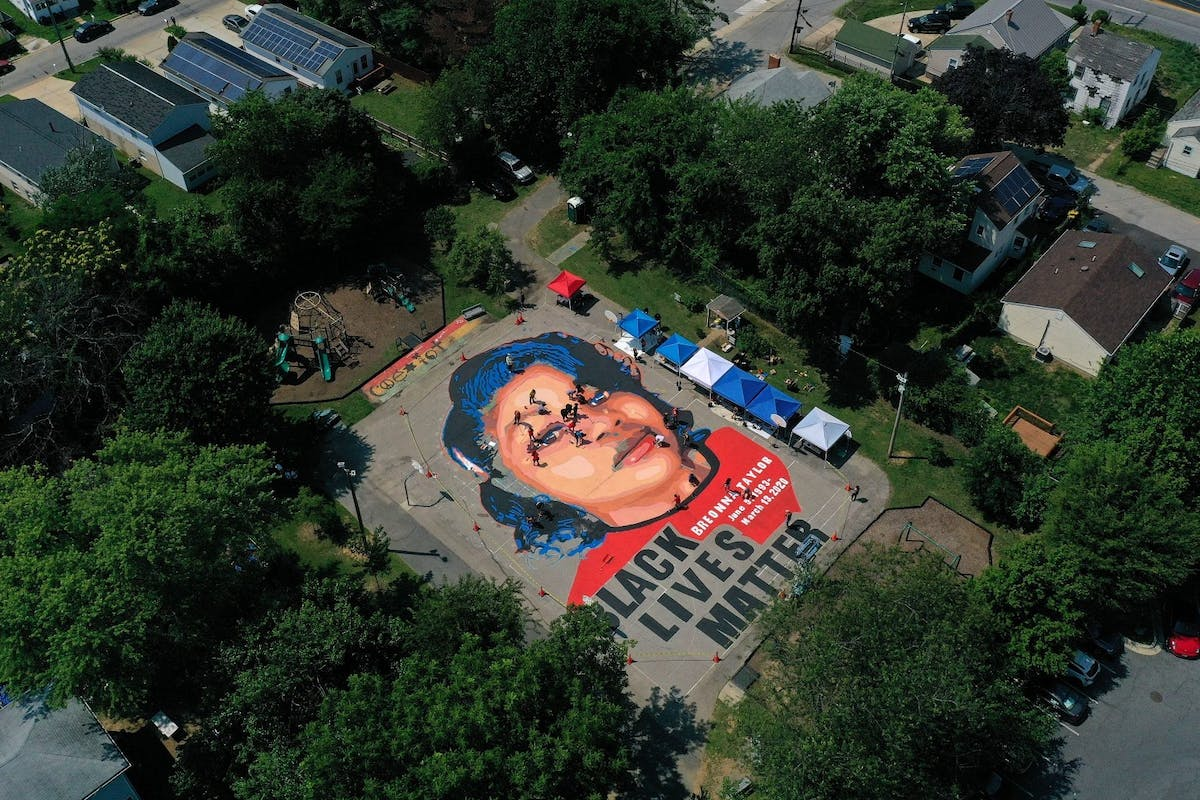 In an aerial view from a drone, a large-scale ground mural depicting Breonna Taylor with the text 'Black Lives Matter' is seen being painted at Chambers Park in Annapolis, Maryland. The mural was organized by Future History Now in partnership with Banneker-Douglass Museum and The Maryland Commission on African American History and Culture.