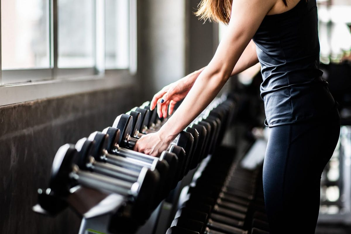 Woman in gym selecting dumbbells