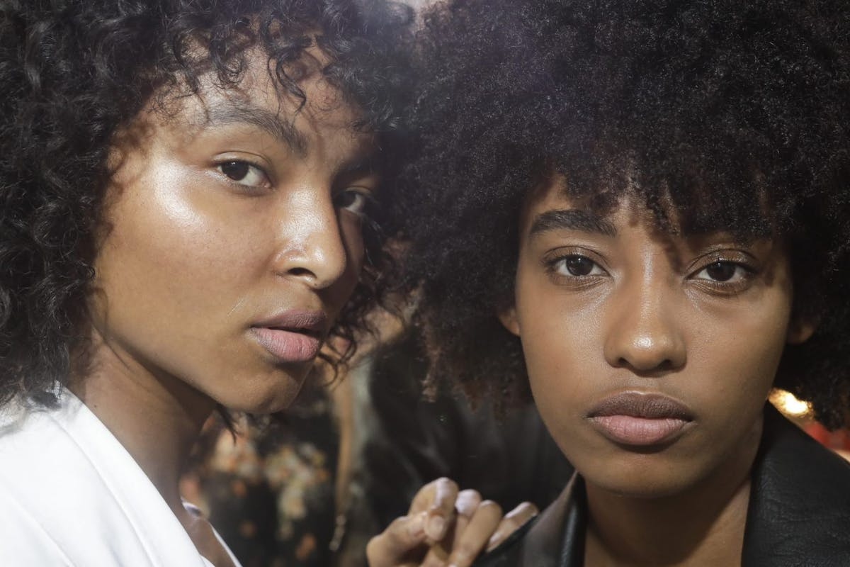 Two models backstage at a fashion show