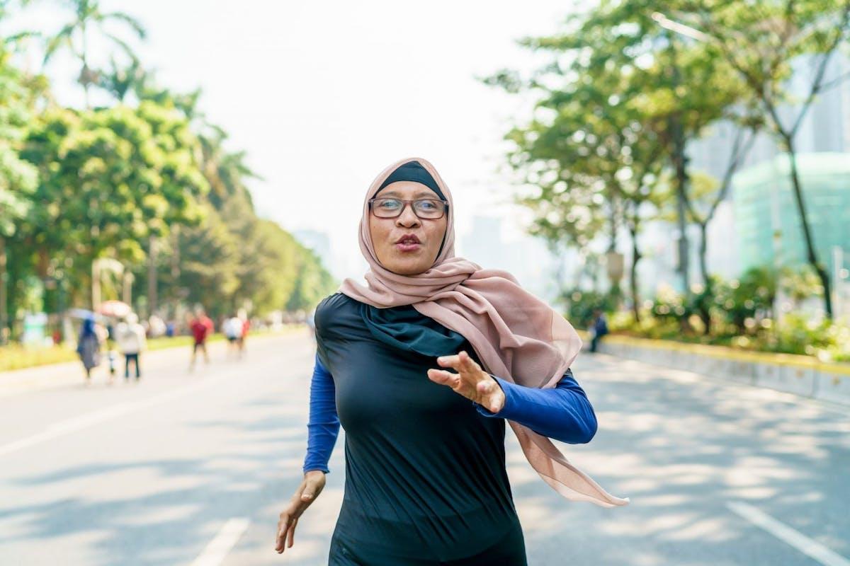 Woman running along an urban road