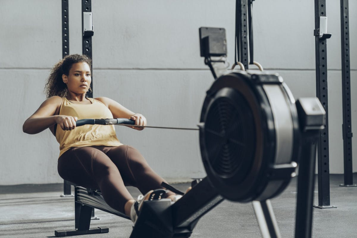 Woman using rowing machine in the gym wearing yellow activewear.
