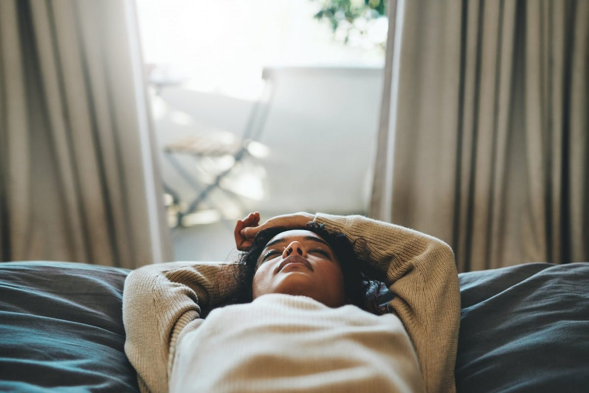 A woman lying on a bed with her eyes closed