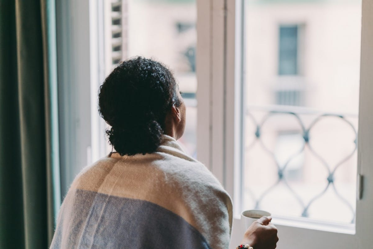 A woman looking at the window and dealing with depression
