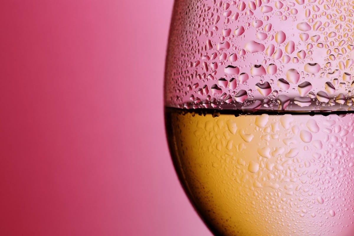 a close up of a wine glass with waterdrops on the outside.