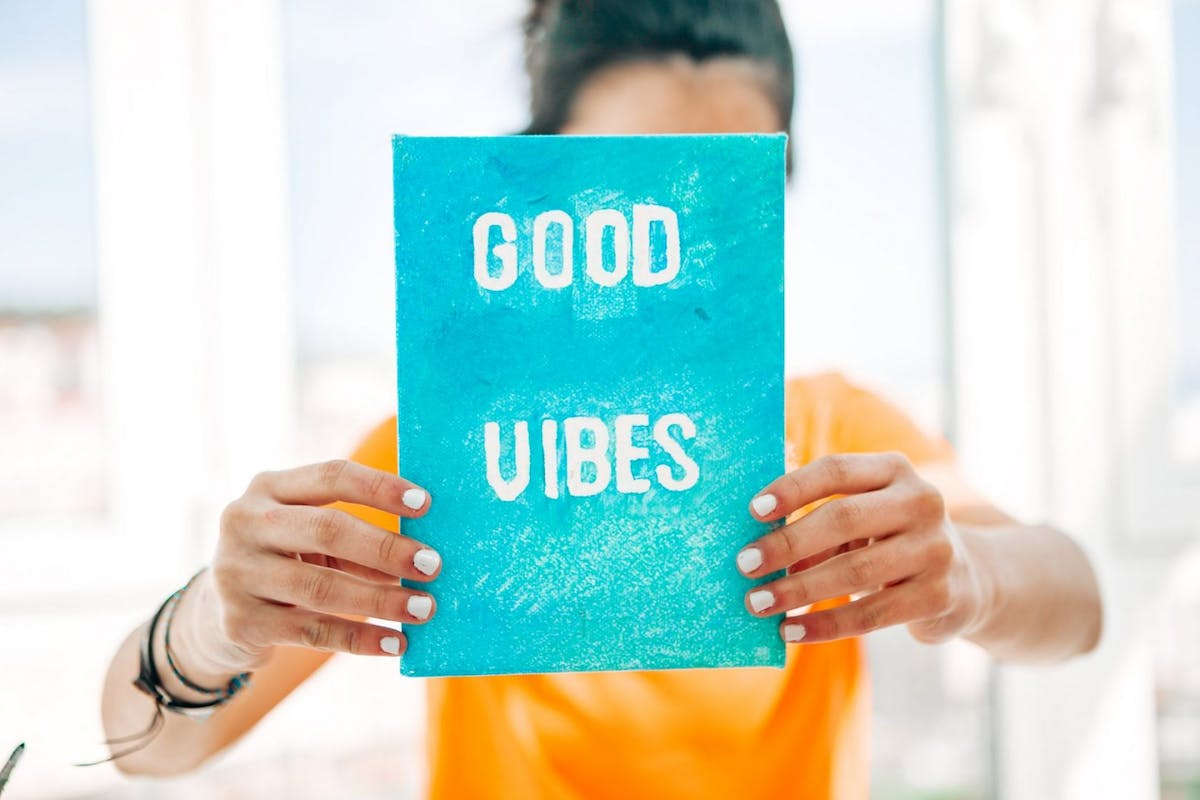 Woman holding book that reads 'Good Vibes'
