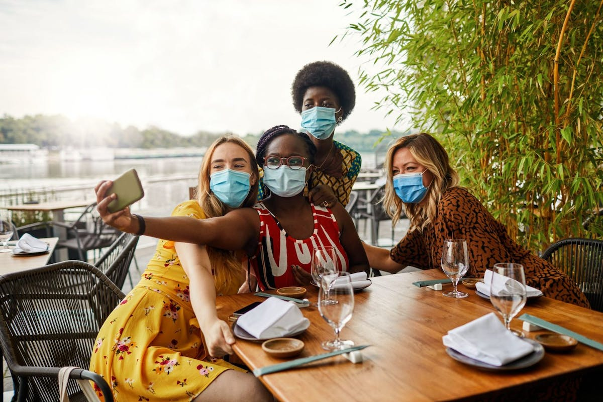 Lockdown rules: Group of young women sitting in restaurant and making selfie. All wear face mask. New normal concept.