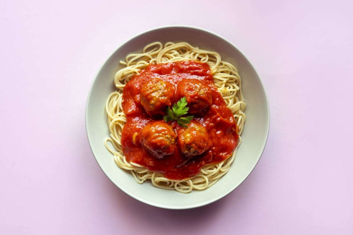Food psychology: Spaghetti with meatballs and tomato sauce on pink background