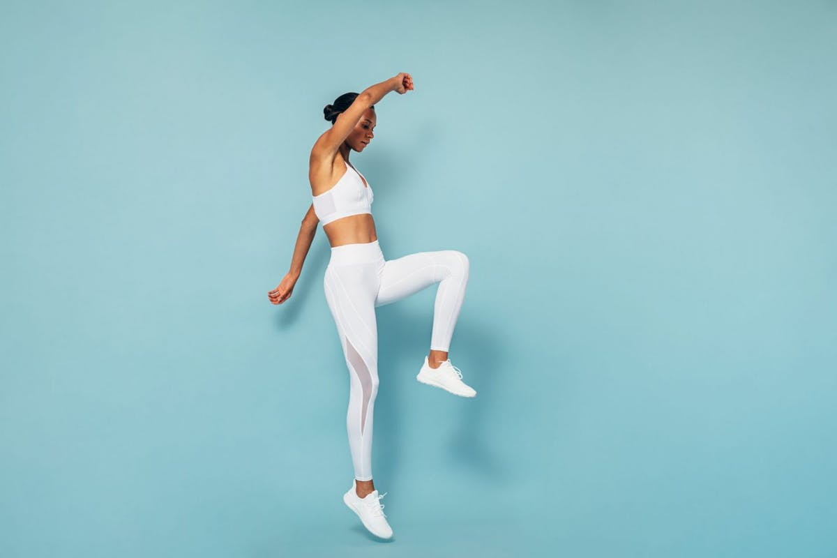 Woman jumping in the air wearing white activewear