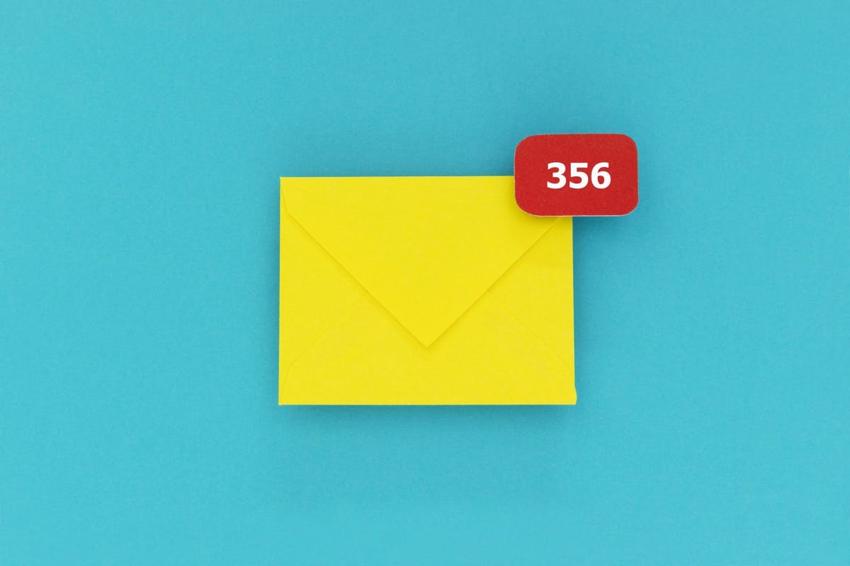 Post-holiday anxiety: Yellow envelope with notification sign with the number 356. Representing accumulated mails in mailbox.