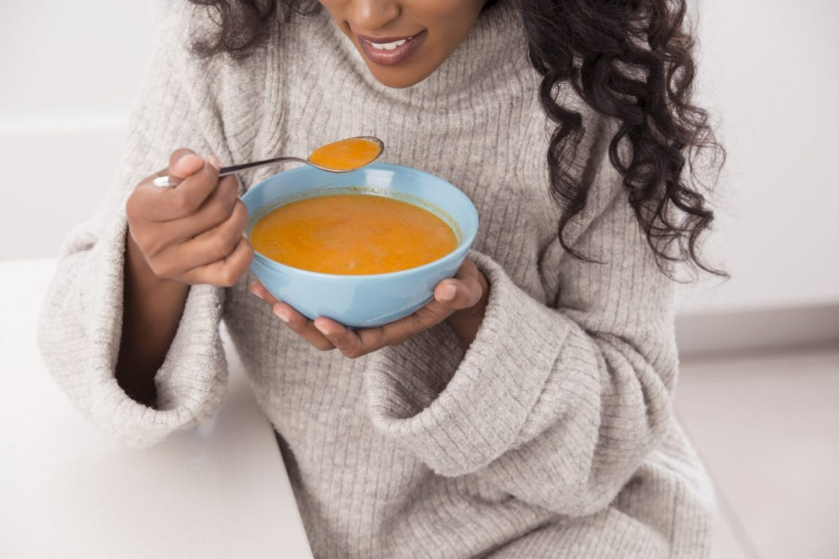 woman in jumper eating soup