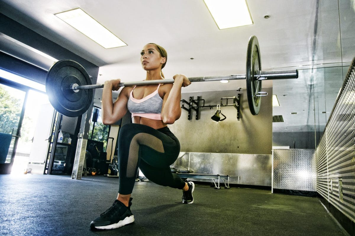 Woman strength training with a barbell