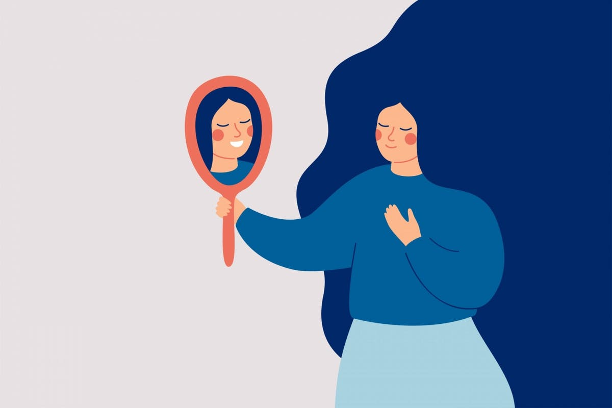 A woman smiling at herself in the mirror