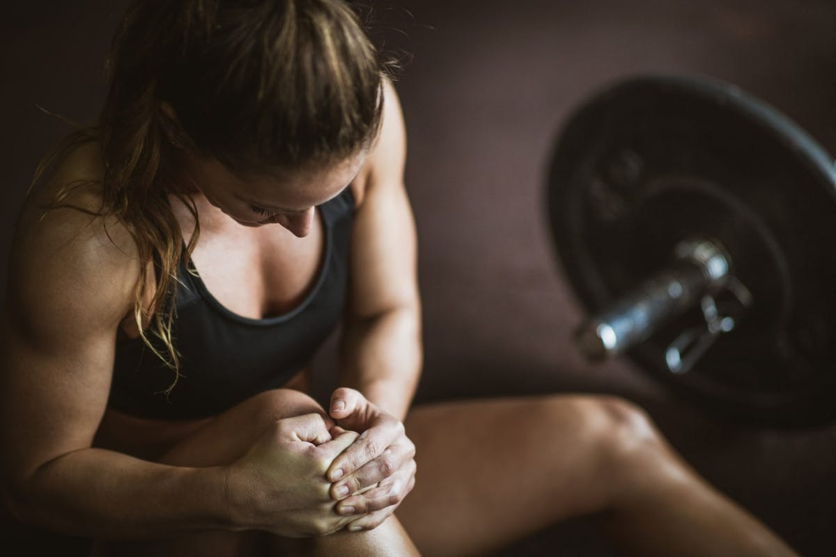 woman weightlifting gym knee injury