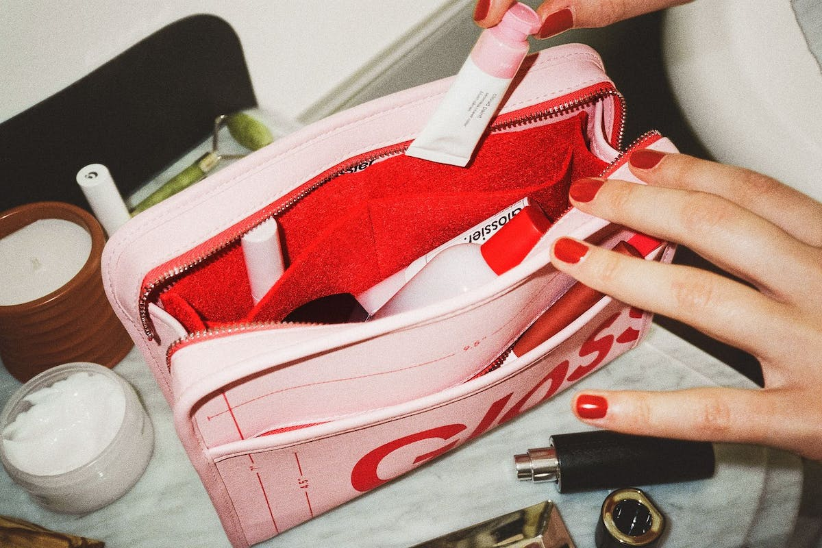 A woman putting make-up into her Glossier Beauty Bag