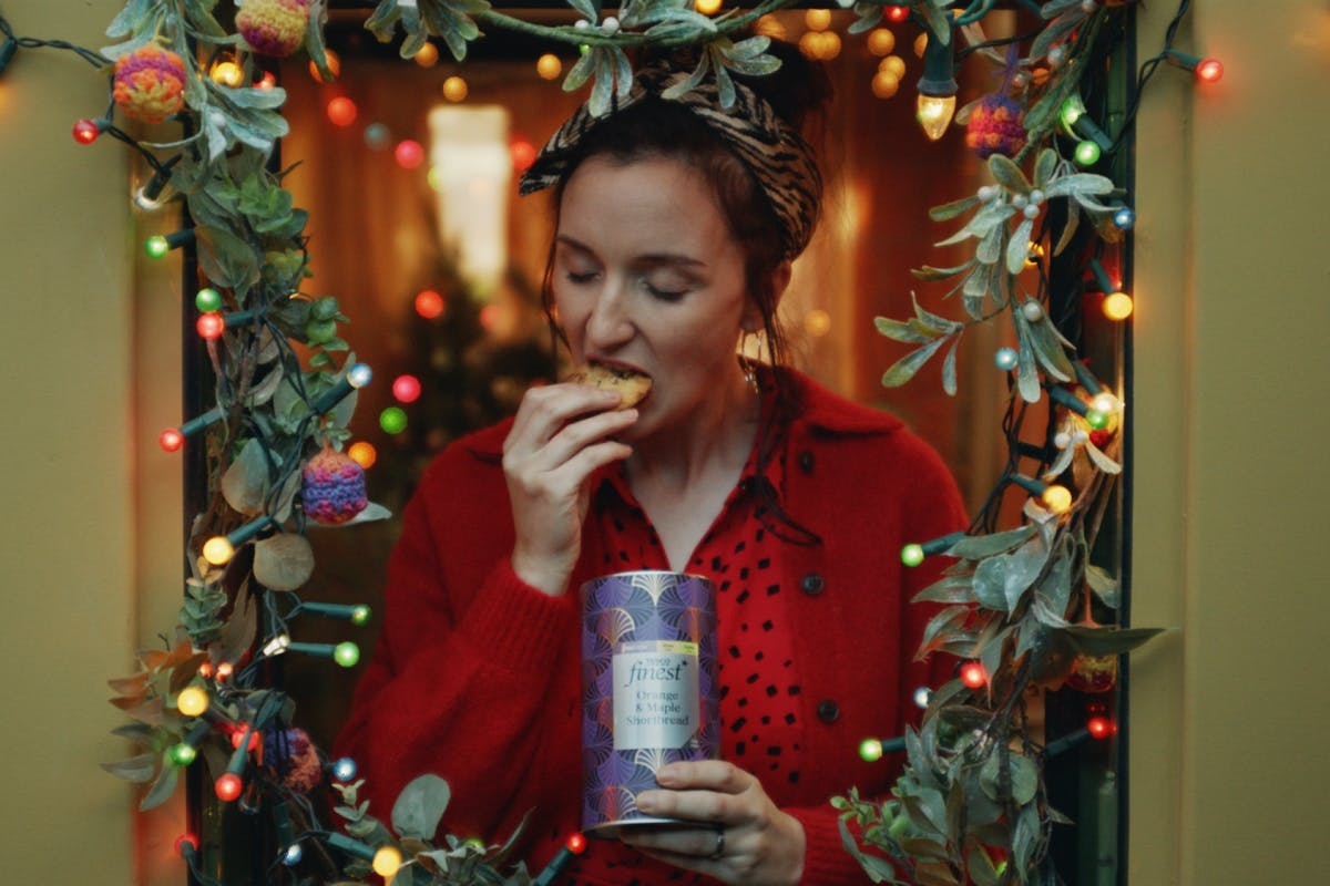 A woman eating a biscuit in Tesco's 2020 Christmas advert