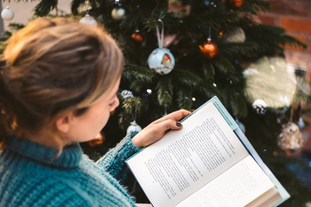 woman reading book by christmas tree