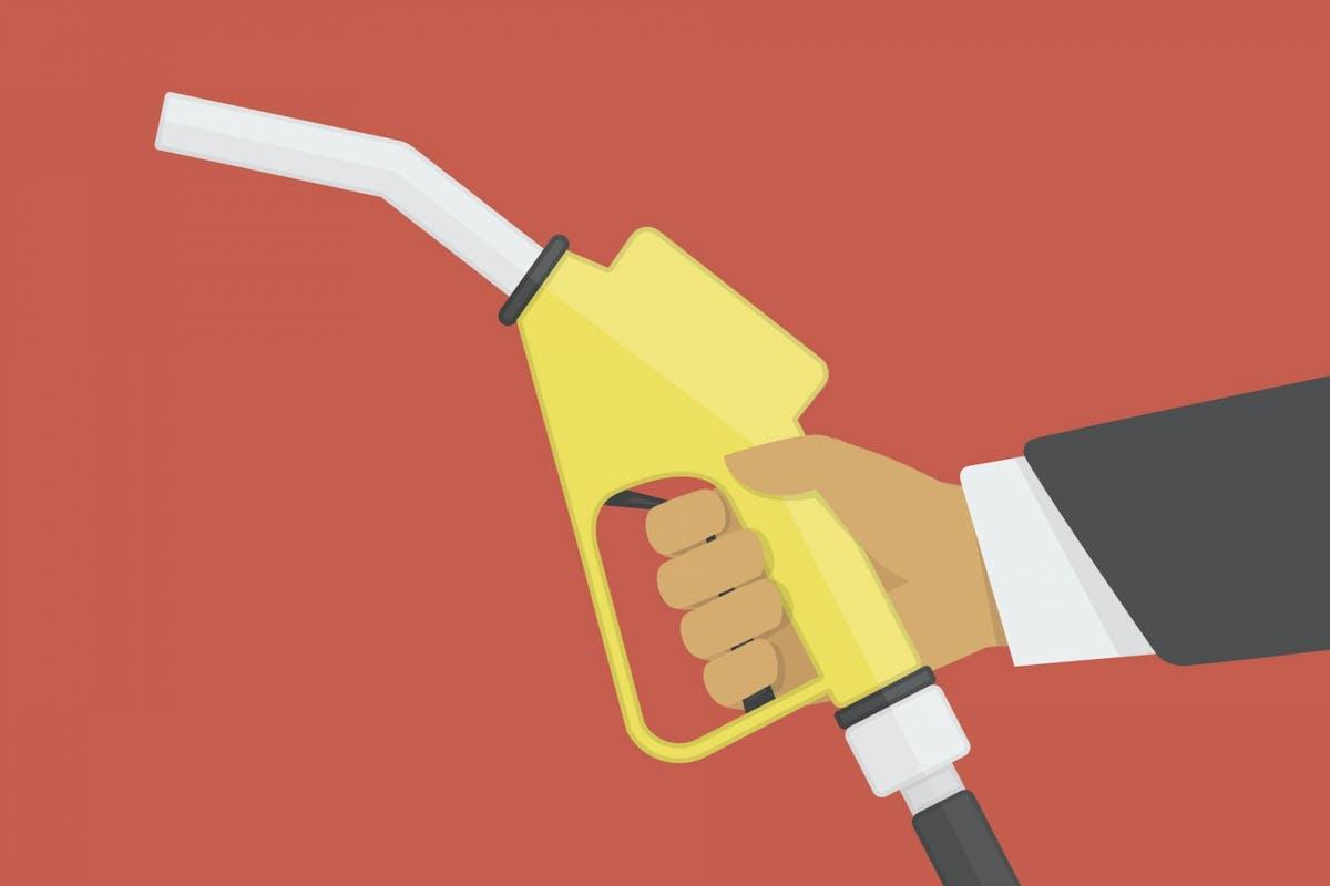 A hand delivering petrol at a petrol pump